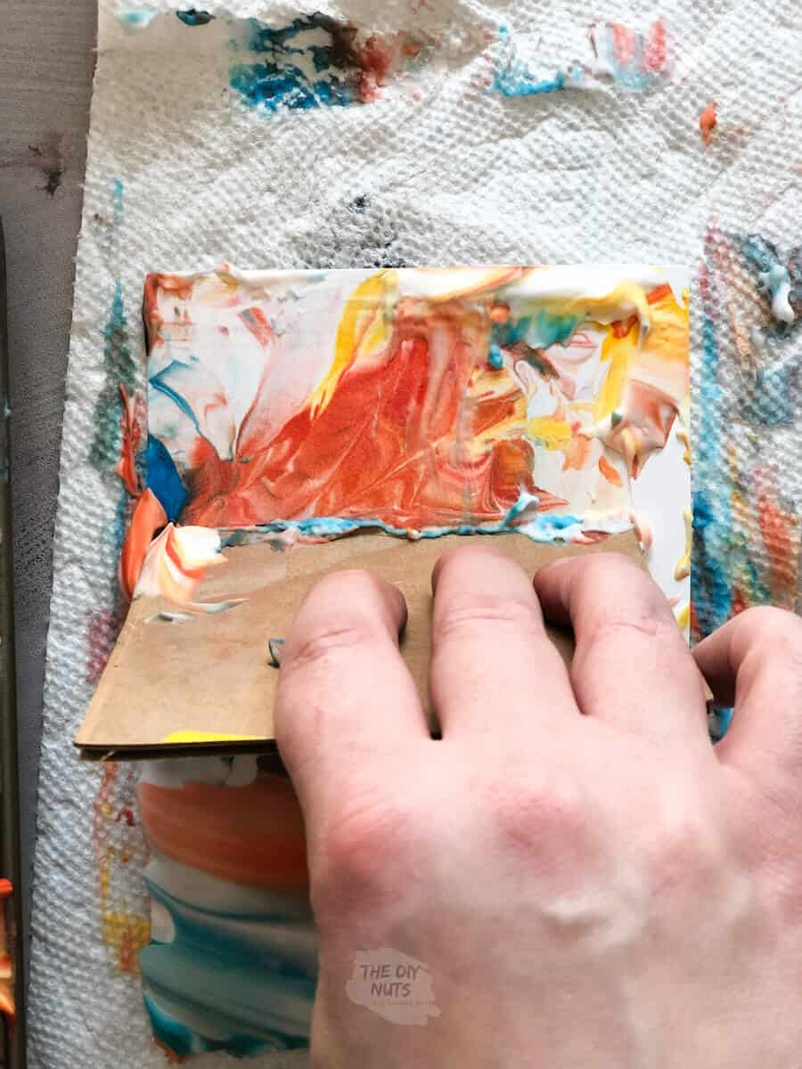 cardboard scraping off marble shaving cream and food coloring