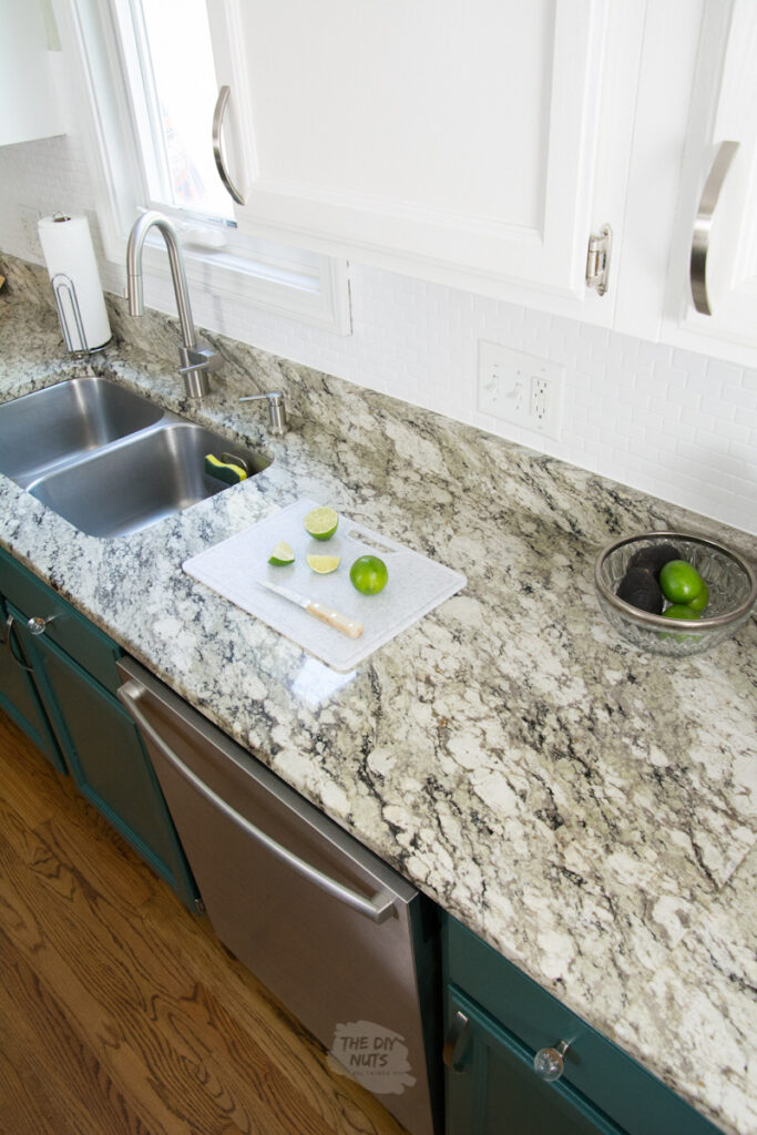 repainted kitchen cabinets and granite countertops and limes on a cutting board