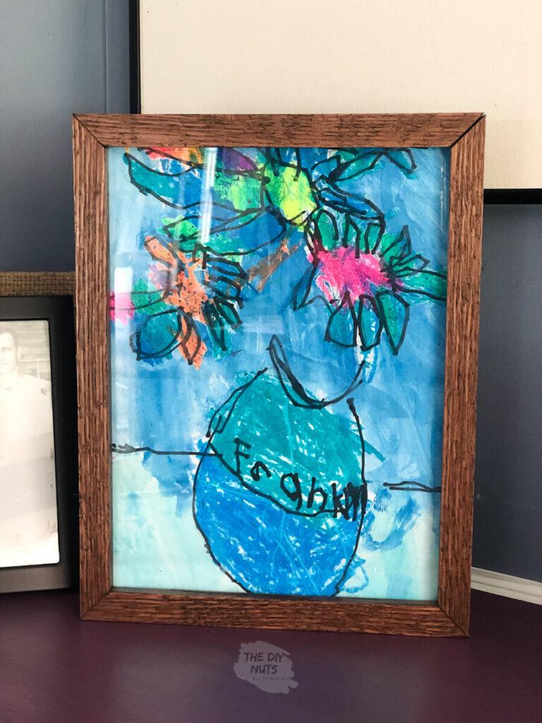 DIY shadow box art storage with child's artwork in it