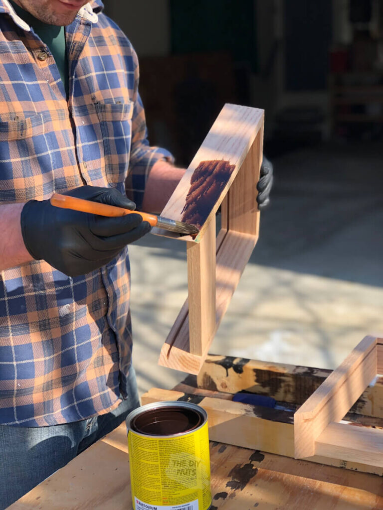 Red mahogany stained being applied to DIY shadow box