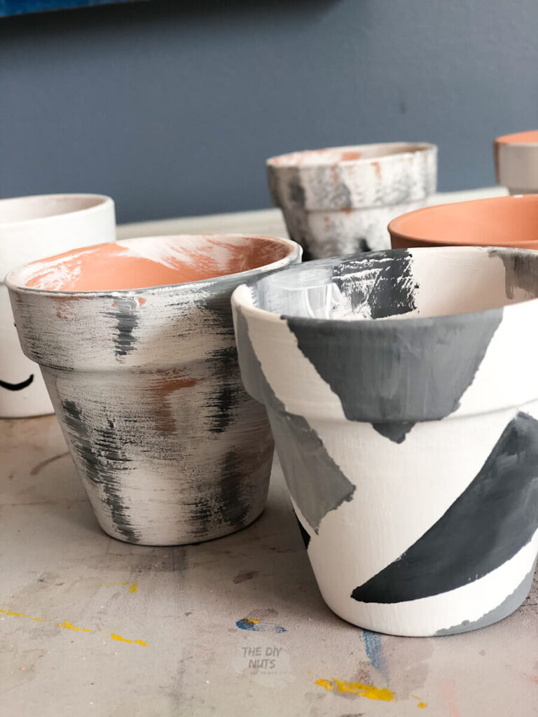 painter's tape used to create diy painted flower pot design