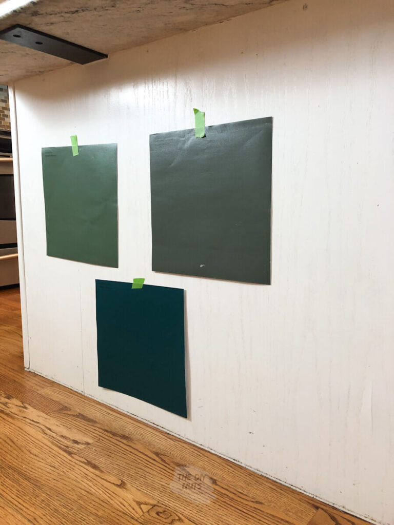 3 green Samplize peel and stick paint samples on cabinet