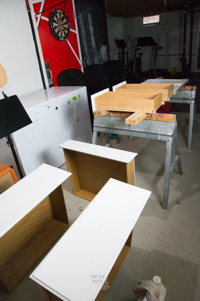 Sawhorses and white painted kitchen cabinet doors and drawers