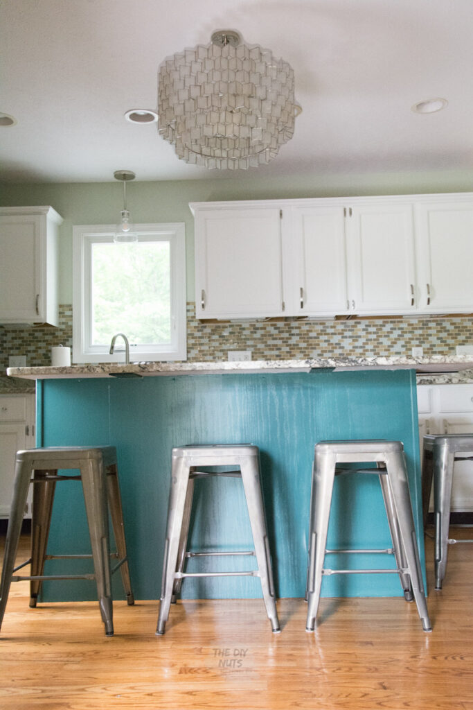 Blue green kitchen island with white upper cabinets