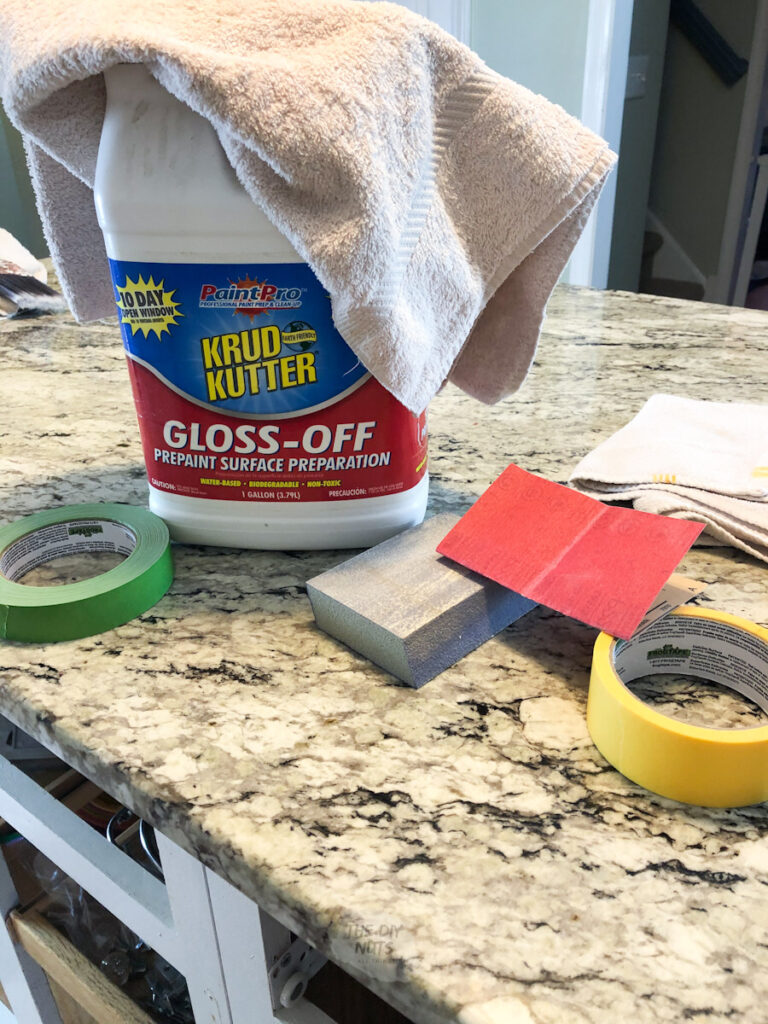 deglosser, painter's tape and extra fine sandpaper on kitchen island
