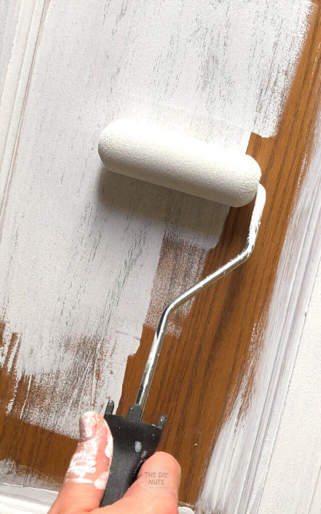 small foam roller apply primer on oak cabinet door
