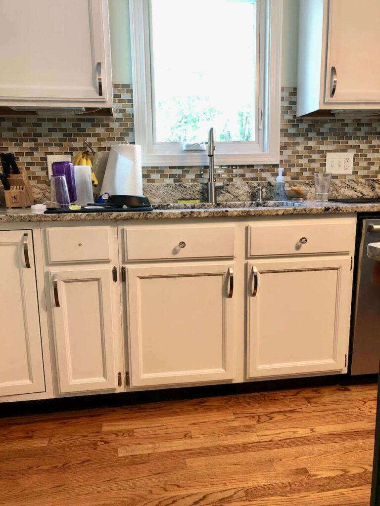 white cabinets and glass backsplash before cheap kitchen makeover