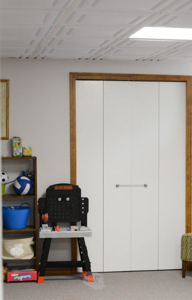 oak molding with white doors and toys in basement and grayish painted walls