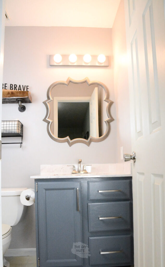 grayish painted walls with charcoal blue painted cabinets with fun shaped silver mirror