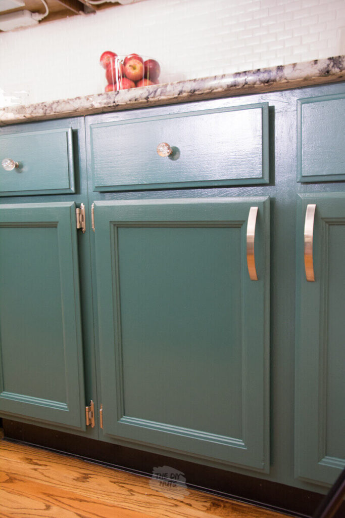 green painted kitchen doors and cabinets with polished nickel hardware and glass knobs