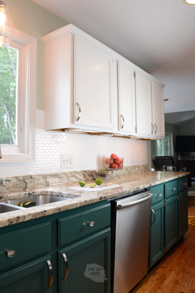 white upper cabinets with green lower and white painted backsplash