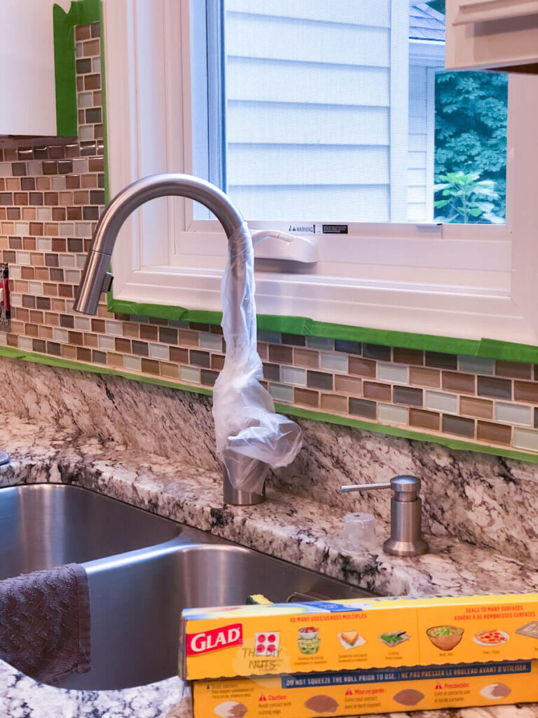 faucet wrapped in Cling Wrap to help with paint prep of tile