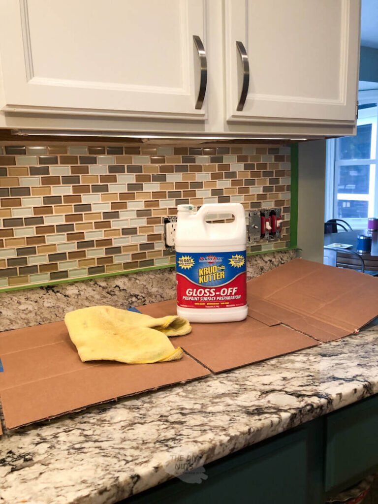 krud kutter and frog tape on counter in front of to-be painted backsplash