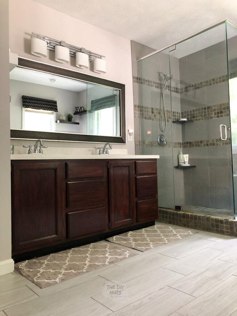 lights off in main bath room with gray tile, dark walnut vanity and grayish walls