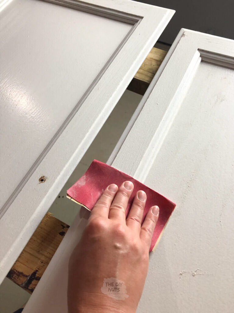 hand using 220 sandpaper before painting cabinets