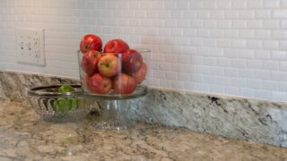 white painted backsplash with red apples on counter in kitchen