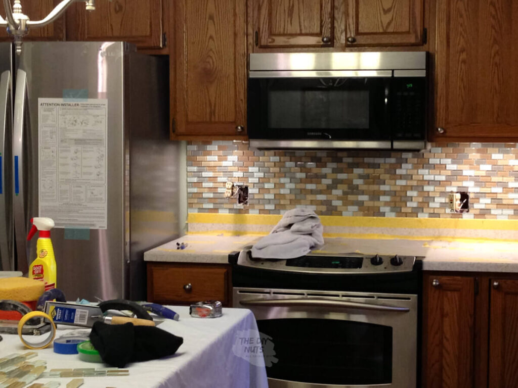 oak kitchen cabinets with glass tile backsplash