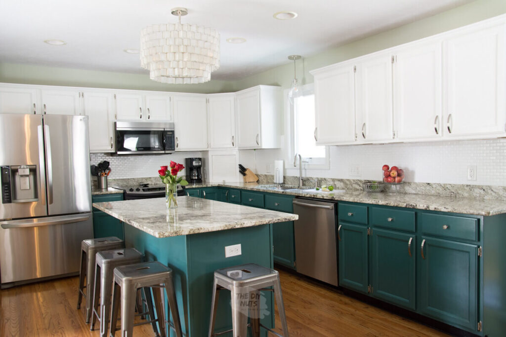 kitchen with white and green cabinets, industrial stools and stainless appliances