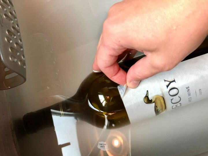 wine label being removed by hand and bottle soaking in baking soda