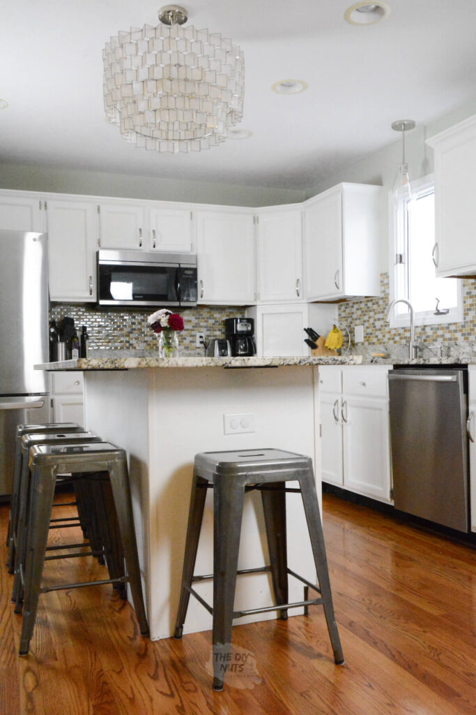 painted white kitchen cabinets with glass mosaic backsplash and capiz shell chandelier