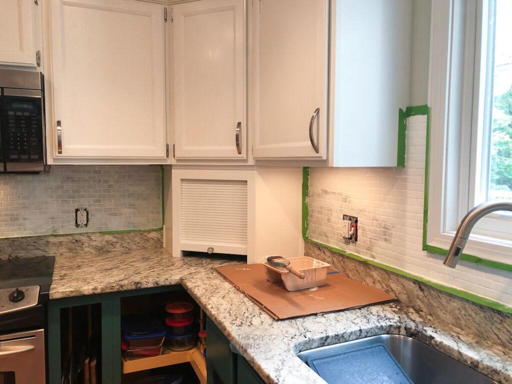 glass tile kitchen backsplash being painted in budget kitchen remodel idea