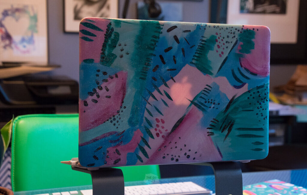 Painted laptop case on computer stand with green chair in the background