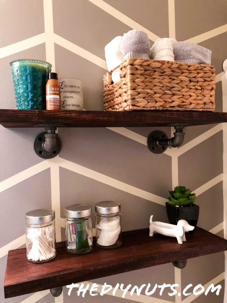 Industrial shelving with basket, towels, jars in bathroom with DIY herringbone accent wall